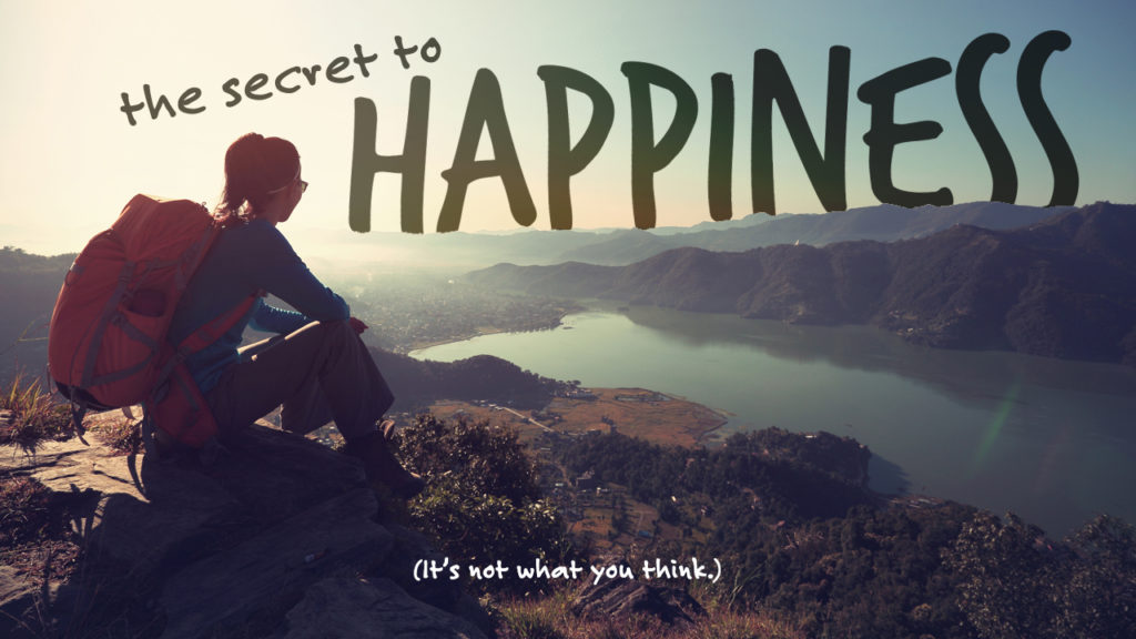 """An image of a woman on top of a mountain looking at the words """"The Secret to Happiness"""". The subtitle is """"It's not what you think."""""""